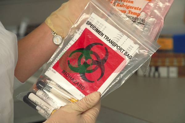 gloved hands holding biohazard bag for transporting specimens