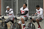 Travion Smith (35), David Davis (97) and Spencer Waseem (29) ride the bikes during Spring football practice at Washington State University under new head football coach, Mike Leach, March 24, 2012.
