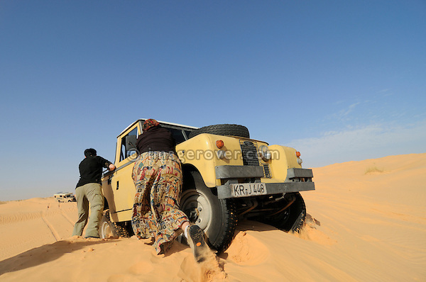 Africa, Tunisia, nr. Tembaine. Doris and Kerstin pushing desert travellers Frank stuck 1964 Land Rover Series 2a Truck Cab back onto firm ground. While traversing sand dunes close to Tembaine on the eastern edge of the Grand Erg Oriental. --- No releases available, but releases may not be needed for certain uses. Automotive trademarks are the property of the trademark holder, authorization may be needed for some uses.  --- Info: Image belongs to a series of photographs taken on a journey to southern Tunisia in North Africa in October 2010. The trip was undertaken by 10 people driving 5 historic Series Land Rover vehicles from the 1960's and 1970's. Most of the journey's time was spent in the Sahara desert, especially in the area around Douz, Tembaine, Ksar Ghilane on the eastern edge of the Grand Erg Oriental.