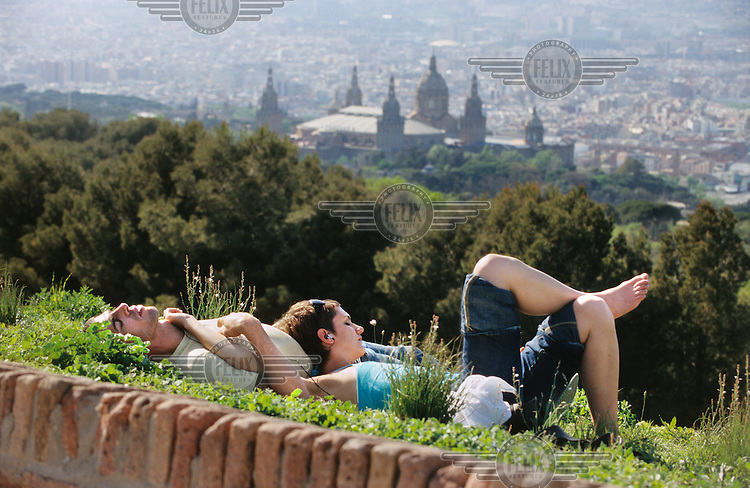 Couple resting on Montjuic, with an impressive view of the city centre. In the background is the Palau Nacional, site of the National Art Museum of Catalonia (MNAC).