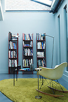"A detail illlustrating one corner of the living room containing a ""Rocking Chair"" by Charles and Ray Eames and the ""Atelier A"" bookshelves constructed from red metal rods dating from 1970 by Francois Arnal"