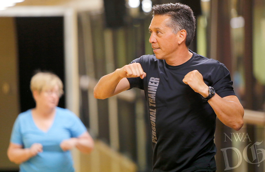 NWA Democrat-Gazette/DAVID GOTTSCHALK - Personal trainer Reuben Reina leads the Young at Heart fitness class at the Fayetteville Athletic Club Monday, July13 , 2015.