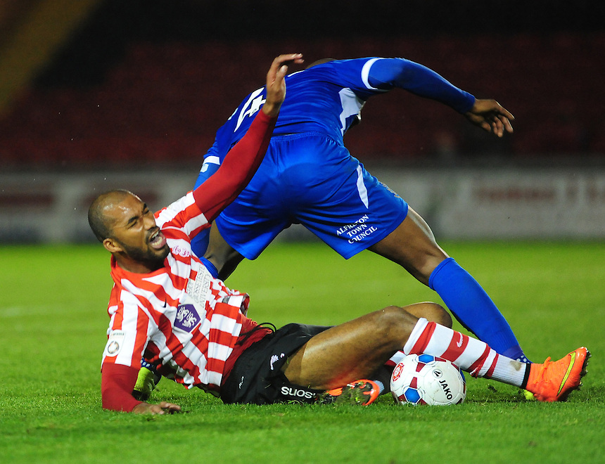 Lincoln City's Delano Sam-Yorke is tackled by Alfreton Town's Duane Courtney<br /> <br /> Photo by Chris Vaughan/CameraSport<br /> <br /> Football - FA Challenge Cup Fourth Qualifying Round replay - Lincoln City v Alfreton Town - Tuesday 28th October 2014 - Sincil Bank - Lincoln<br /> <br /> &copy; CameraSport - 43 Linden Ave. Countesthorpe. Leicester. England. LE8 5PG - Tel: +44 (0) 116 277 4147 - admin@camerasport.com - www.camerasport.com