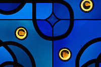 Detail of the stained glass window in blue glass with interlacing patterns in lead reminiscent of the Neo-Romanesque period of the 19th century, made by Ateliers Loire, Chartres, in the Upper Chapel, themed as 'L'Engagement' or Commitment, in Le Tresor de la Cathedral d'Angouleme, in Angouleme Cathedral, or the Cathedrale Saint-Pierre d'Angouleme, Angouleme, Charente, France. The 12th century Romanesque cathedral was largely reworked by Paul Abadie in 1852-75. In 2008, Jean-Michel Othoniel was commissioned by DRAC Aquitaine - Limousin - Poitou-Charentes to display the Treasure of the Cathedral in some of its rooms, which opened to the public on 30th September 2016. Picture by Manuel Cohen. L'autorisation de reproduire cette oeuvre doit etre demandee aupres de l'ADAGP/Permission to reproduce this work of art must be obtained from DACS.
