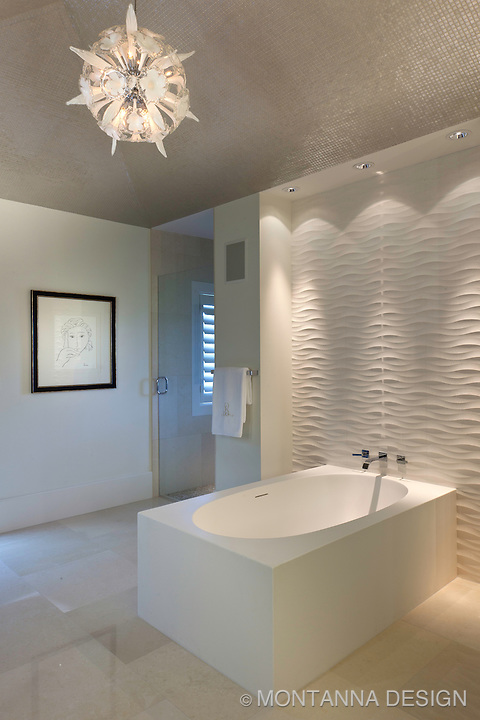 The round glass chandelier makes the glass mosaic ceiling sparkle, down lights wash the wall for interesting shadows on the textured architectural panels at the tub