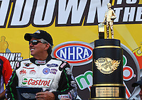 Sep 13, 2013; Charlotte, NC, USA; NHRA funny car driver John Force stands next to the championship trophy during qualifying for the Carolina Nationals at zMax Dragway. Mandatory Credit: Mark J. Rebilas-