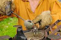 Pewtersmith pours molten pewter into a brass button mold to make a set of four buttons, at a Revolutionary War encampment, Old Sturbridge Village, Massachusetts, USA.