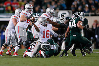 Ohio State Buckeyes quarterback J.T. Barrett (16) throws away the ball to avoid being sacked by Michigan State Spartans safety Demetrious Cox (7) during Ohio State's 49-37 win over Michigan State in the NCAA football game at Spartan Stadium in East Lansing, Michigan on Nov. 8, 2014. Barrett was called for intentional grounding on the play. (Adam Cairns / The Columbus Dispatch)