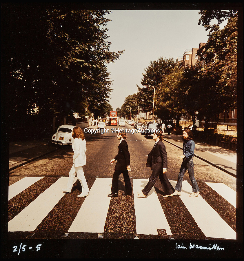 BNPS.co.uk (01202 558833)<br /> Pic: HeritageAuctions/BNPS<br /> <br /> A rare set of the iconic images of the Beatles crossing Abbey Road shot for the cover of their world famous album have emerged at auction.<br /> <br /> The complete set of six out-take photos, which were rejected as possible covers, is one of only five sets of prints that were made from the fully uncropped negatives, making it particularly rare.<br /> <br /> The snaps were taken by Scots photographer Iain Macmillan, a close friend of John Lennon, who balanced precariously on a ladder in the middle of the road in north London while a willing policeman held up and directed traffic on the busy Abbey Road on August 8, 1969.<br /> <br /> The pictures have an estimate of £63,000 but experts at Heritage Auctions in New York say they could sell for hundreds of thousands on October 27.