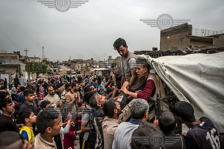 Residents of a recently recapured area of western Mosul queue up for food being distributed by a local volunteer organisation.
