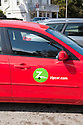 A close up of a red car by the car sharing company Zip Car in a parking lot in Bolinas. Customers pay by the hour or day to use the car which have dedicated parking spaces in cities. Bolinas, California, USA
