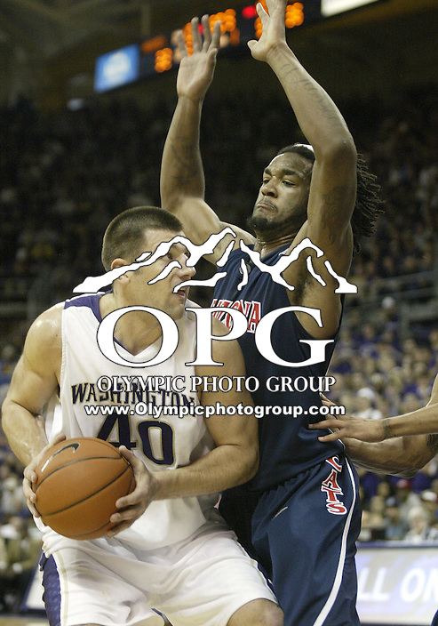 28 February 2009:  Washington Husky forward #20 Jon Brockman looks for a opening to the basket as Arizona's #43 Jordan Hill guards him at the Bank of America Arena at Hec Edmundson Pavilion in Seattle, WA.  Washington won 83-78 over  Arizona.