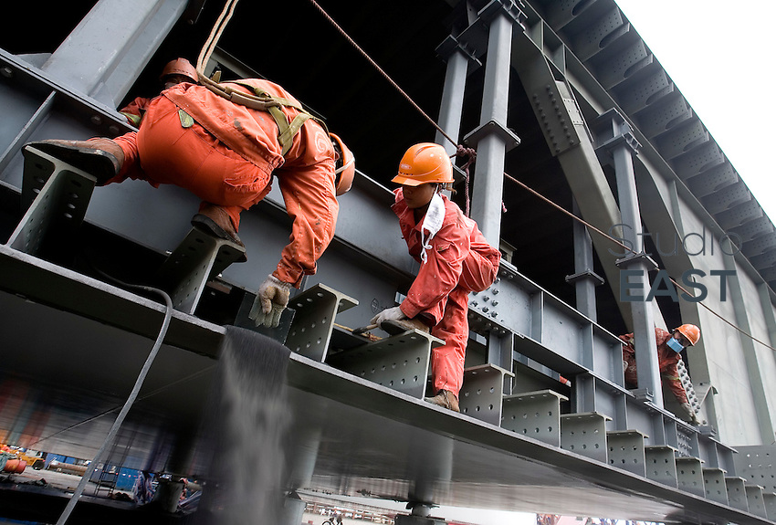 Workers work on OBG 4BW standing on the trial assembly of Self-Anchored Suspension (SAS) bridge outside the workshops of Shanghai Zhenhua Port Machinery Co. Ltd. (ZPMC), on Changxing Island, Shanghai, on September 24, 2009. Photo by Lucas Schifres/Pictobank