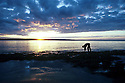 Person looking in tide pools. Lone figure on beach. Scottish Rocks at low tide. Sunset. Booderee (formerly Jervis Bay) National Park. NSW.