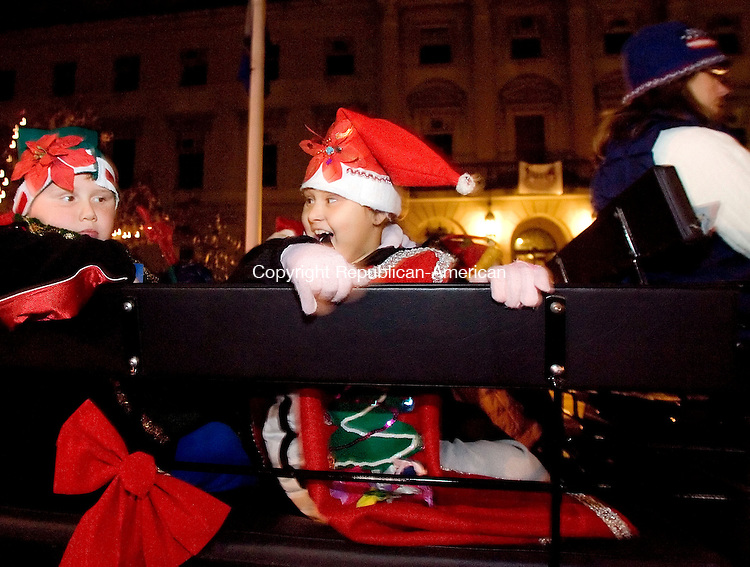 WATERBURY, CT- 25 NOV 2007- 112507JT03- <br /> Natalie Resto, 9, looks to Josh Somma, 8, as they and other Santa's helpers begin their horse-pulled ride from Chase Municipal Building on Grand Street  to the Waterbury Green Sunday during the annual tree-lighting ceremony.<br /> Josalee Thrift / Republican-American