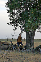A hunter waiting for doves under a tree and in proximity to water