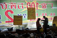 A couple look at discounted designer-style handbags and purses in a partially-demolished storefront in Nanjing, Jiangsu, China.