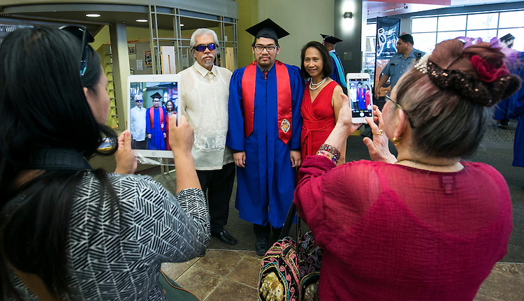 CDM graduate Edward Bote poses for family photos as students and their families gather with faculty and staff for the Baccalaureate Mass Friday, June 10, 2016. The event was part of the 118th commencement ceremonies for the Chicago university. (DePaul University/Jamie Moncrief)