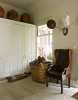 The boot room which adjoins the kitchen is furnished with a built-in cupboard
