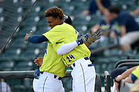 Second baseman Walter Rasquin (22) of the Columbia Fireflies is hugged by Jose Medina (24) after hitting his first home run of the season against the Augusta GreenJackets on Thursday, July 11, 2019 at Segra Park in Columbia, South Carolina. Columbia won, 5-2. (Tom Priddy/Four Seam Images)
