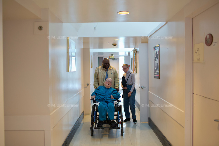 Dorothy Rouleau (right) walks alongside as caregiver Jean Castor pushes resident Margaret Rouleau, 84, down a hallway in her residence at Malone Park at the Fernald Center in Waltham, Massachusetts, USA.  Margaret is one of the few residents who can speak.  Margaret is Dorothy's sister.