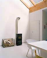 A small wood burning stove in the dining area of the large open-plan artist's studio