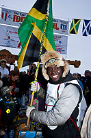 The first ever Jamaican musher, Newton Marshall, holds the Jamaican flag at the finish line in Nome during the 2010 Iditarod