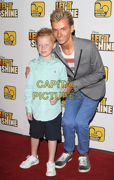 Freddie Derbidge & Harry Derbidge.The 'Let It Shine' VIP screening, May Fair Hotel, London, England..July 16th, 2012.full length blue white grey gray suit jacket red striped top jeans denim shirt black shorts bending leaning brothers siblings family.CAP/ROS.©Steve Ross/Capital Pictures.