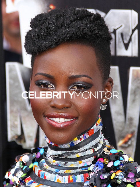 LOS ANGELES, CA, USA - APRIL 13: Actress Lupita Nyong'o wearing a turtle neck short-sleeved black and white tee-length dress by Chanel (Fall/Winter 2014 Collection), earrings by Vita Fede and bright blue pointed toe heels by Casadei arrives at the 2014 MTV Movie Awards held at Nokia Theatre L.A. Live on April 13, 2014 in Los Angeles, California, United States. (Photo by Xavier Collin/Celebrity Monitor)