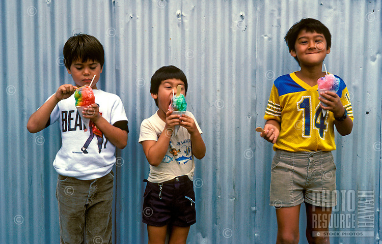 Three boys enjoy their shave ice cones, popular island treat.