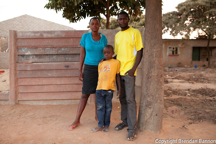 "Seven Year-old Brian Tom with his mother, Eselina Mtali and his step-father Muchaneta  Chiparawasha, at home in Epworth, Zimbabwe at dusk. Brian Tom (7) is a patient enrolled in the MSF HIV/AIDS project in Epworth, an urban settlement adjacent to the capital Harare of Zimbabwe. ""The doctor gives me pills that I have to take in the afternoon and the evening. They are white and blue and they taste and I don't know what they are for. In school, I like music and singing and I want to be a pilot when I grow up."".With 14.3 per cent prevalence rate (UNAIDS 2009), Zimbabwe is one of the countries worst affected by the worldwide HIV/AIDS epidemic. Since 2007, MSF has been running an HIV/AIDS project in Epworth. In August 2011, MSF had 12,864 patients under care in both of its clinics there."