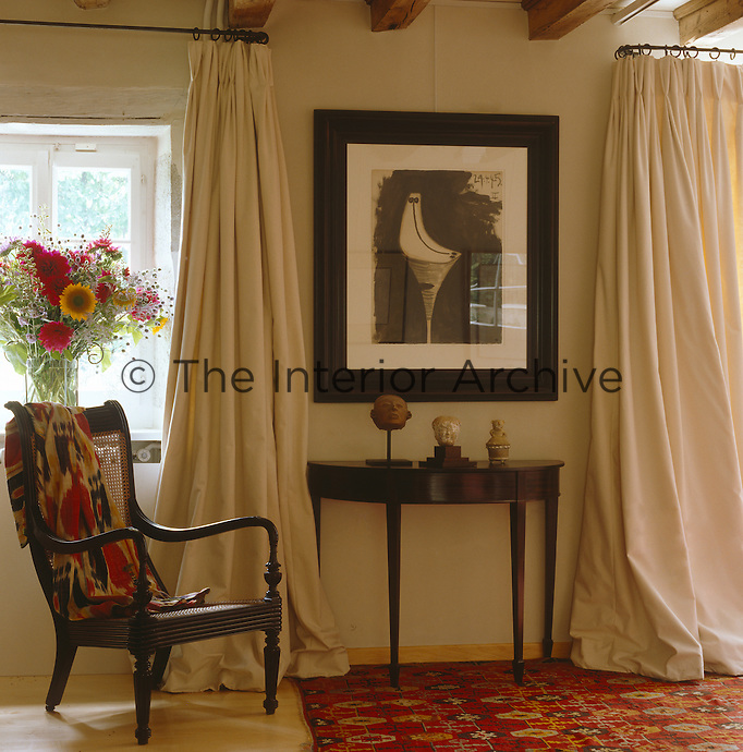 Simple white cotton curtains on wrought-iron poles flank a modern pen and ink artwork