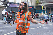 24/08/2014. London, England. A photographer is covered in paint. Notting Hill Carnival 2014 starts with the traditional early-morning J'ouvert or Jouvet parade down Ladbroke Grove where revellers throw paint and flour.