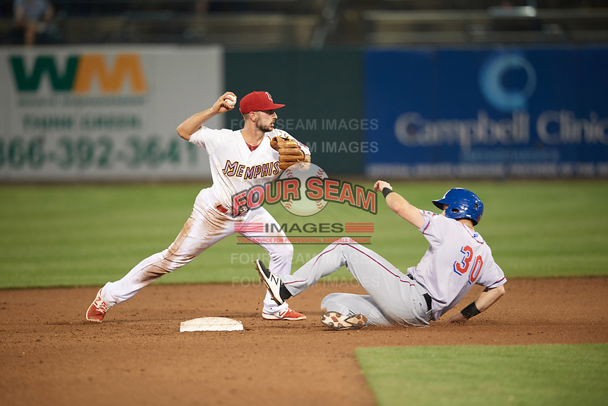 Memphis Redbirds shortstop Paul DeJong (11) throws to first base as Jared Hoying (30) slides into second base during a game against the Round Rock Express on April 28, 2017 at AutoZone Park in Memphis, Tennessee.  Memphis defeated Round Rock 9-1.  (Mike Janes/Four Seam Images)