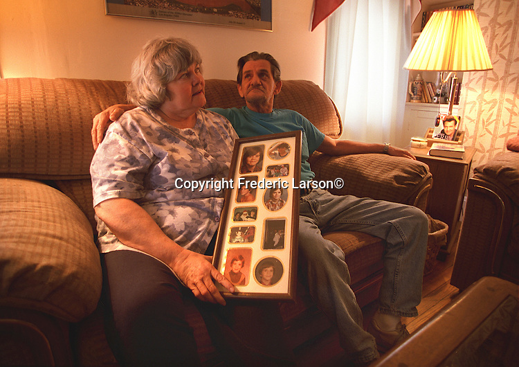 Louise (holding a collection of photographs of her son Jimmy) and James Cox parents of Jimmy Cox (29) who was homeless and died in San Francisco.  Argyle before his death by a Muni train was inimate with Valery.  Both sleeping on store front steps to stay out of the rain on Haight Street.