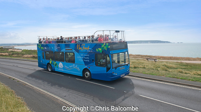 New Forest Tour open-top Bus driving along Milford On Sea seafront, with the Isle of Wight and The Needles (right) in the distance.<br /> <br /> Pic: Chris Balcombe