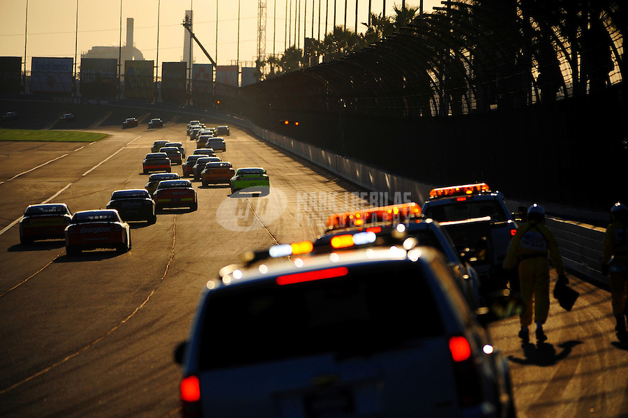 Aug 31, 2008; Fontana, CA, USA; NASCAR Sprint Cup Series drivers head down the backstretch as safety crews clean up the track during a caution in the Pepsi 500 at Auto Club Speedway. Mandatory Credit: Mark J. Rebilas-