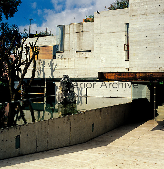 A raised pool at the rear of the house casts reflections and light onto the concrete walls of the property