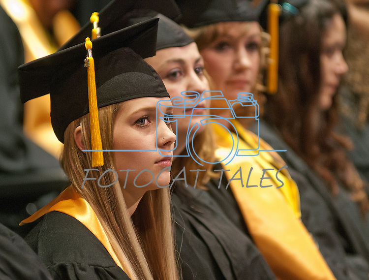 WNC students Kim Moore, left, Stephanie Bishop and Brittany Esposito listen to the commencement address at the Western Nevada College commencement in Fallon, Nev., on Tuesday, May 20, 2014. <br /> Photo by Kim Lamb