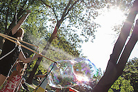 Girl blows a soap bubble that pops during a soap bubble day in a public park in Budapest, Hungary on August 19, 2012. ATTILA VOLGYI