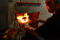 "Heating a cooper kettle (""annealing""). Gyokusendo, Tsubame, Niigata Pref, Japan, August 24, 2017. Traditional copper metalworking company Gyokusendo was founded in 1816 and is a registered as a traditional craft of Japan. At Gyokusendo, in a highly-skilled craft process, complex items such as teapots are beaten from a single sheet of copper using hammers and hundreds of other specialist tools."