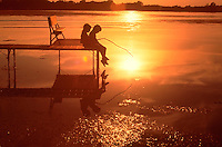 Silhouette of two 7 year old cousins fishing and talking on the dock.  Lake Kegonsa  Wisconsin USA