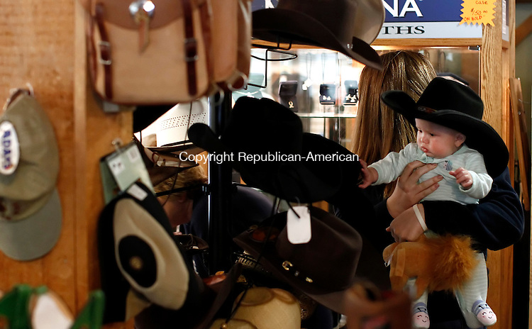 Bethlehem, CT- 23 May 2014-052314CM01- Brie Gustafson of Woodbury plays with her cousin,  Ruby Capodiferro, 6 months old of Watertown, as she tries on a cowboy hat at Annie Oakley's store in Bethlehem on Friday.  The frontier store will be holding a sale before closing its doors .   Christopher Massa Republican-American