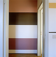 Wide horizontal bands of colour enliven the wall of an otherwise dark corridor