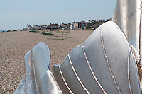 """Scallop"" a sculpture to celebrate Benjamin Britten by Maggie Hambling.  Made specifically for this site on the Suffolk coast which inspired so much of Britten's music.  The phrase, ""I hear those voices that will not be drowned"" (pierced through the steel against the sky), is taken from Britten's opera ""Peter Grimes"", which was itself based on a work by the Aldeburgh poet, George Crabbe.  Looking towards Aldeburgh."