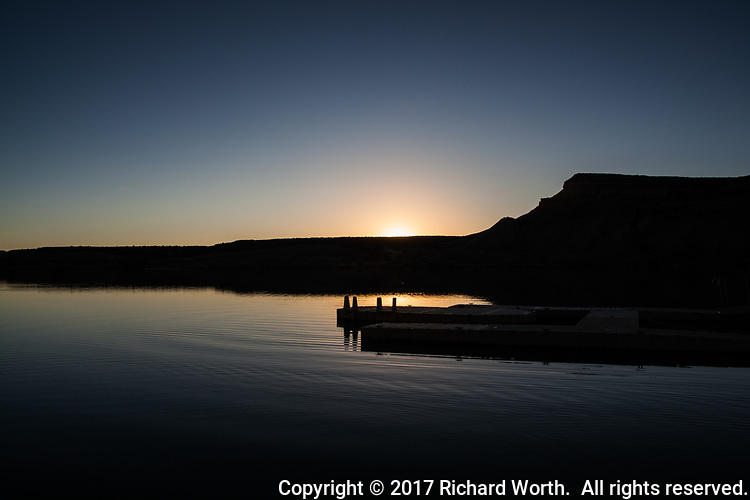 The sun has barely slipped below the horizon at a mountain lake with an empty boat dock and clear blue sky.