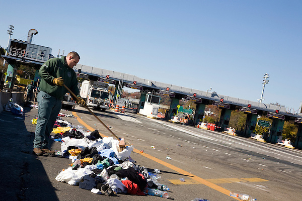 A city worker gathers discarded clothing and other trash littering the on-ramp to the Verrazano-Narrows Bridge after the start of the ING New York City Marathon on Staten Island on 07 November 2010.