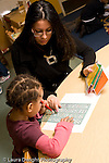 Education Preschool 3-4 year olds female student teacher working with boy writing letters with stencil , holding alphabet cards for him vertical