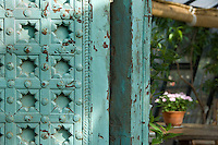 Detail of an Indian antique carved and painted door inside a greenhouse at Petersham Nursery