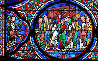 The apostles carry the coffin of Mary to her funeral in Jerusalem, while the Jewish high priest in the centre raises his hand, which withers when it touches the coffin. On the left, 2 apostles, one holding a palm frond, possibly St John. The Funeral of Mary, from the Glorification of the Virgin stained glass window, in the nave of Chartres Cathedral, Eure-et-Loir, France. This window depicts the end of the Virgin's life on earth, her dormition and assumption, as told in the apocryphal text the Golden Legend of 1260. Chartres cathedral was built 1194-1250 and is a fine example of Gothic architecture. Most of its windows date from 1205-40 although a few earlier 12th century examples are also intact. It was declared a UNESCO World Heritage Site in 1979. Picture by Manuel Cohen